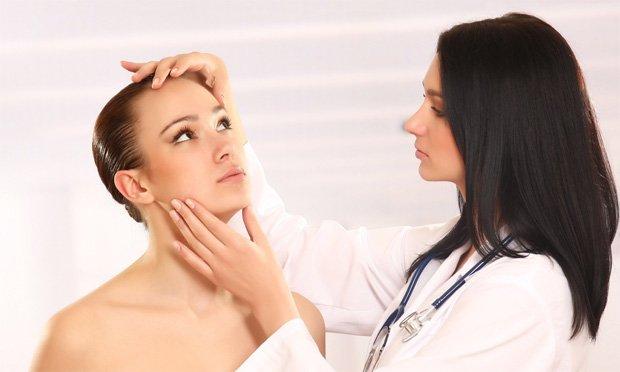 Женщина врач пристально осматривает лицо молодой пациентки