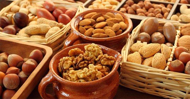 На столе в разных емкостях большое разнообразие орехов