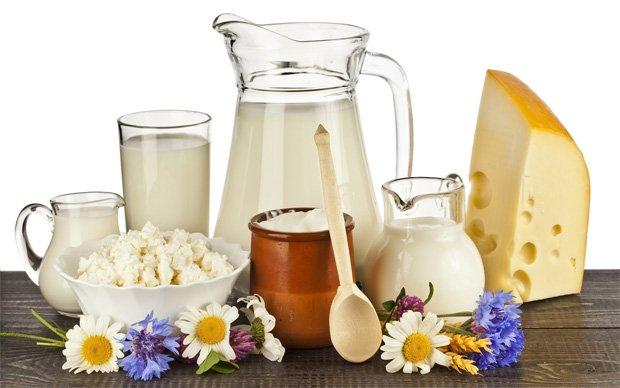 На столе стоят кувшины с молочными продуктами, сыр, сметана, творог