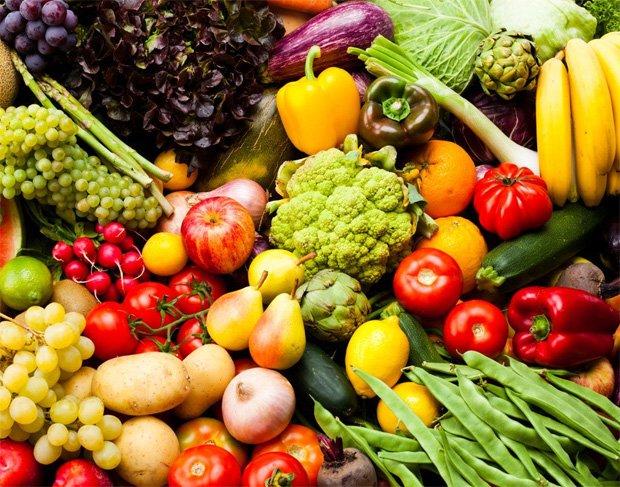На поверхности лежит большое ассорти из различных фруктов и овощей