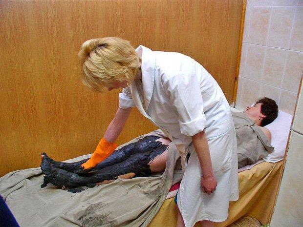 Медицинская сестра в санатории обмазывает пациентку нефтяной мазью