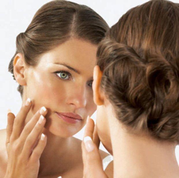 Девушка с красивой прической наносит на лицо масло перед зеркалом