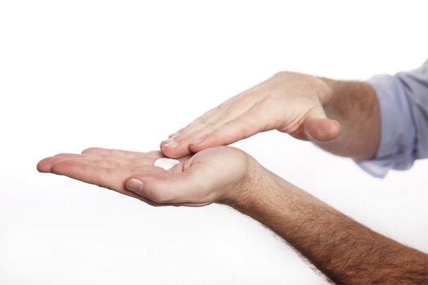 Человек распределяет по ладони лекарственный крем