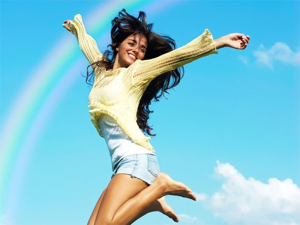 Счастливая девушка подпрыгивает на фоне радуги