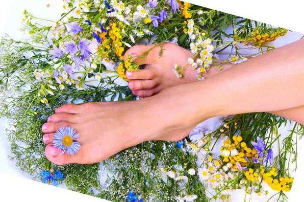 Девушка держит ноги в растворе из лечебных трав
