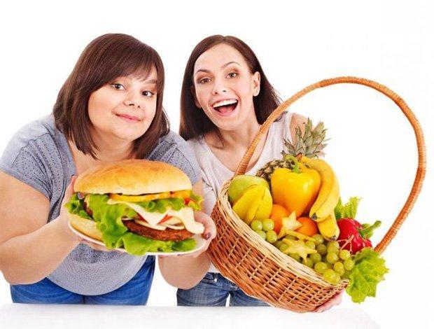 Полная девушка держит тарелку с гамбургером, а худая корзину с фруктами