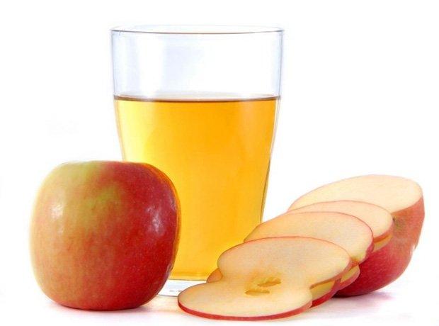 На столе стакан с яблочным уксусом, целое и нарезанное яблоко