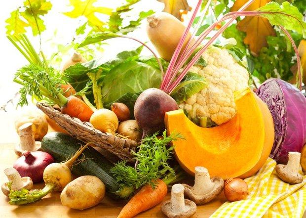 На столе стоит корзина с полезными фруктами и овощами для диеты