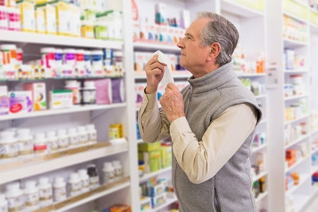Мужчина стоит в аптеке и разглядывает полки с препаратами