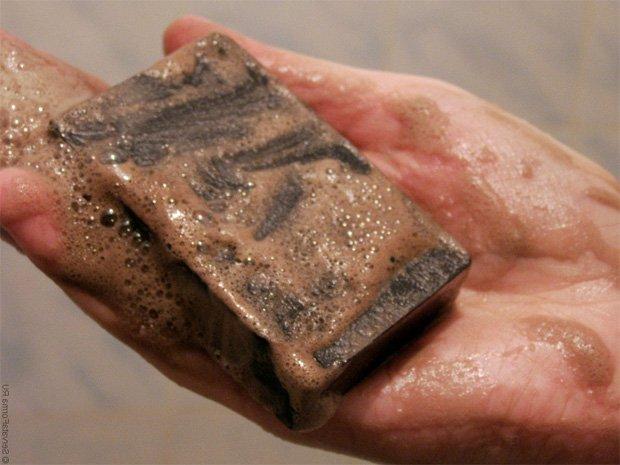 Человек держит в руке пенный кусок дегтярного мыла