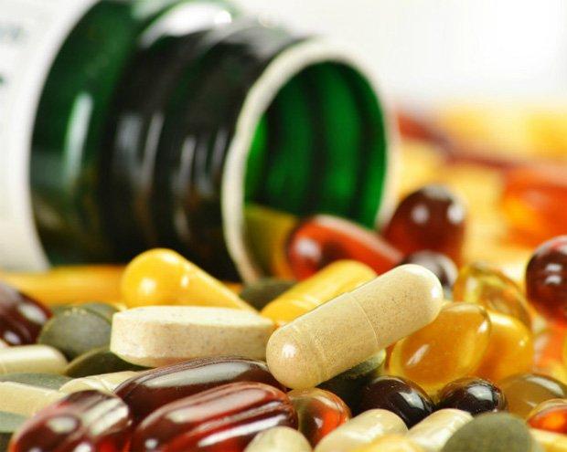 На столе опрокинутая открытая баночка на фоне множества лекарств