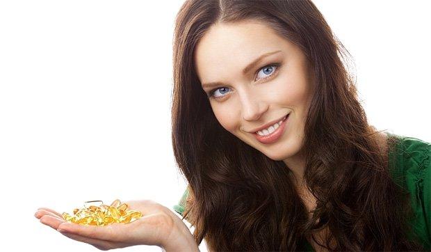 Девушка держит на ладони горсть капсул с рыбьим жиром