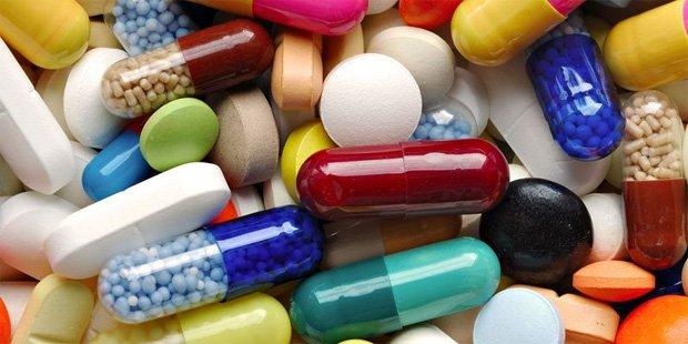 На столе рассыпано большое разнообразие цветных таблеток