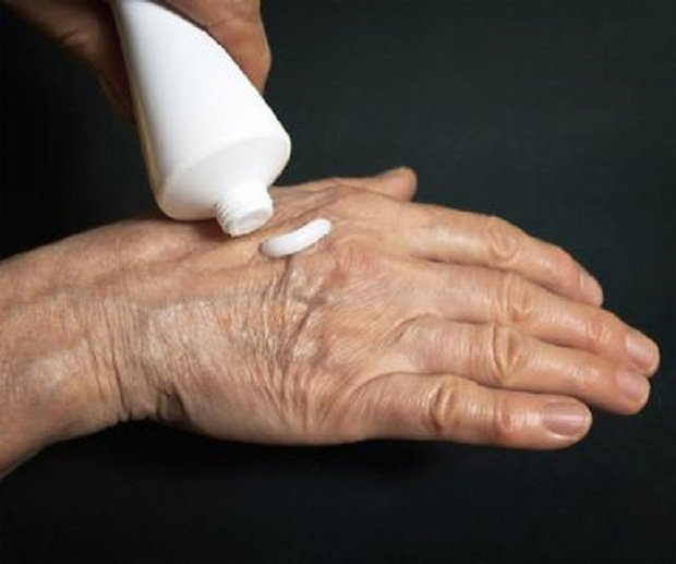 Пожилой человек выдавливает из тюбика лечебную мазь на руку