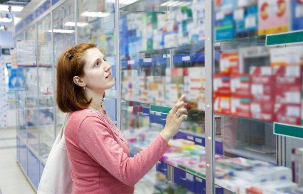 Девушка в аптеке выбирает мазь для лечения кожи головы