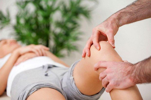 Врач осматривает ногу лежащей на кушетке пациентки