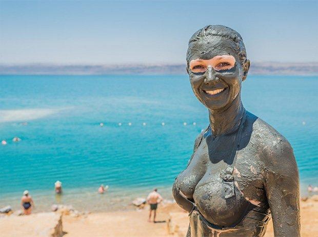 На берегу моря стоит девушка, полностью покрытая лечебной грязью