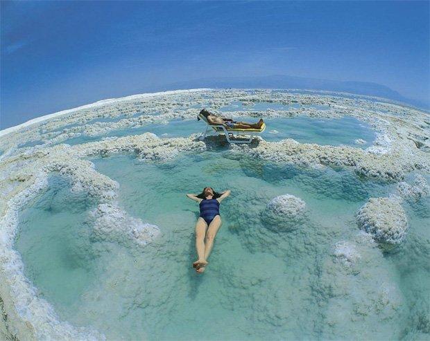 Девушка и молодой человек лежат на поверхности воды мертвого моря