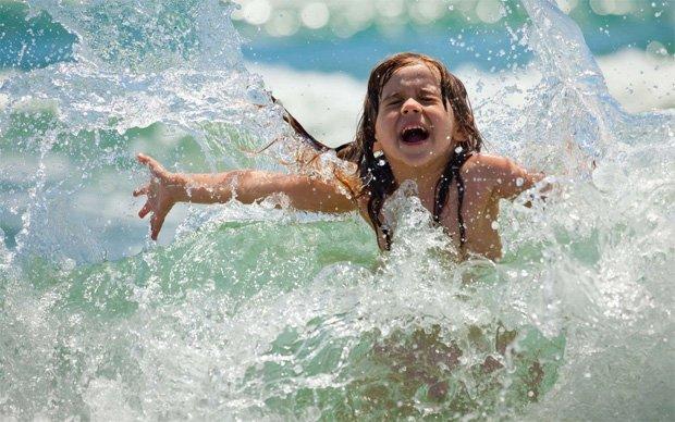 Счастливая девочка зажмурилась от брызг воды азовского моря