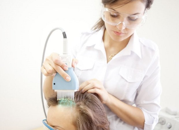 Врач проводит пациенту процедуру облучения псориаза на голове