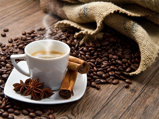 На столе рассыпаны кофейные зерна из мешка и стоит чашка с кофе