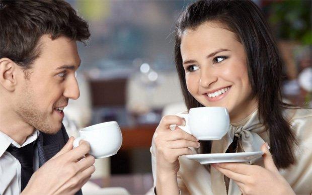 Молодая девушка с парнем пьют кофе из белых чашек