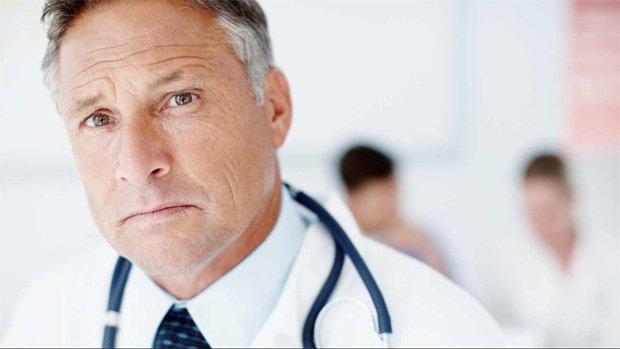 Врач в белом халате и стетоскопом на фоне других врачей