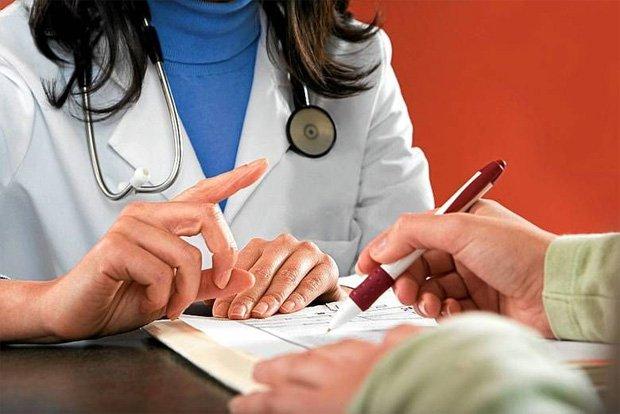 Женщина врач в белом халате дает на подпись пациенту документы