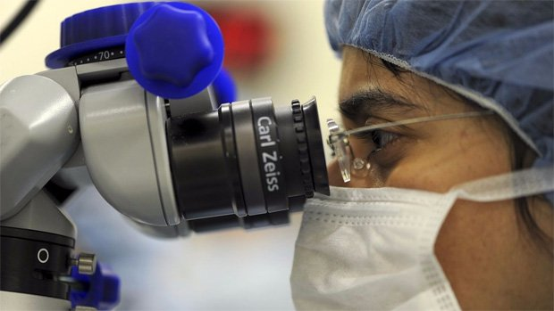 Лаборант рассматривает в микроскоп вирусные клетки