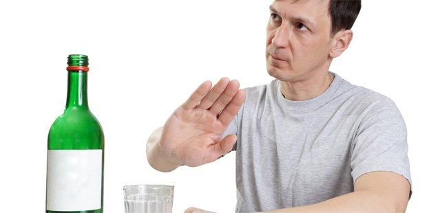 Мужчина жестом показывает отказ от спиртных напитков
