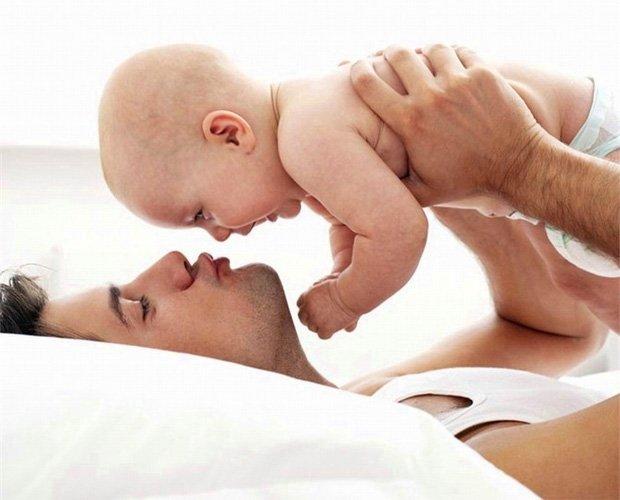 Молодой папа играет со своим ребенком на кровати