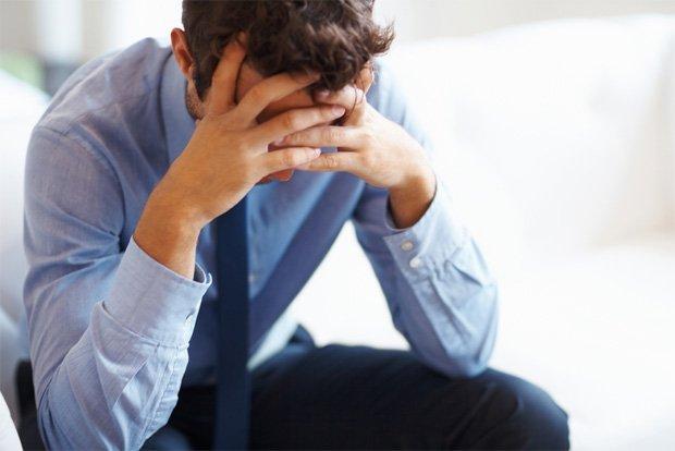 Расстроенный мужчина сидит и придерживает голову руками