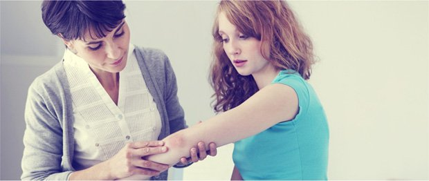 Женщина осматривает локоть девушки с высыпаниями