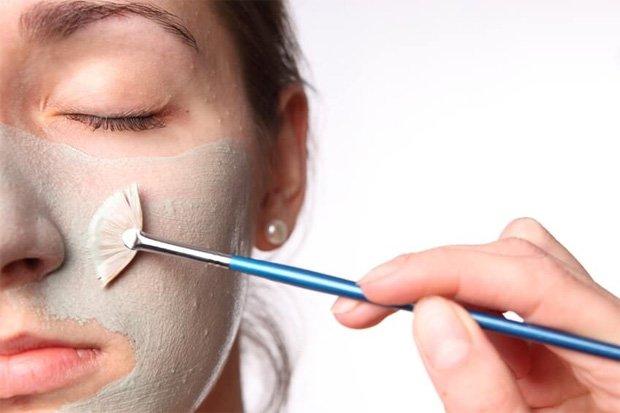 Девушка наносит на лицо лечебную смесь кисточкой