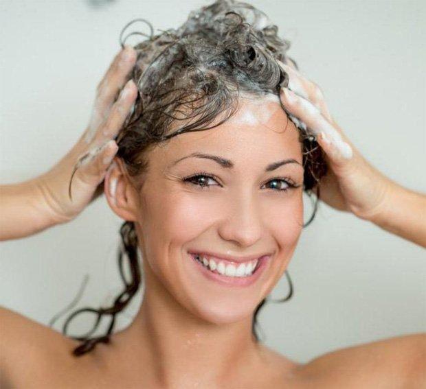 Девушка моет голову лечебным шампунем и улыбается
