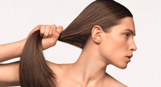 Девушка со здоровой кожей головы держит себя за волосы